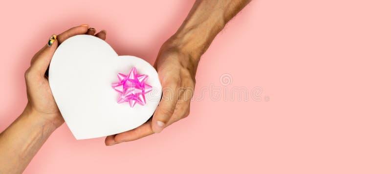 Vue supérieure des mains masculines et femelles tenant le boîte-cadeau de coeur de forme avec l'arc rose sur la configuration pla photo stock