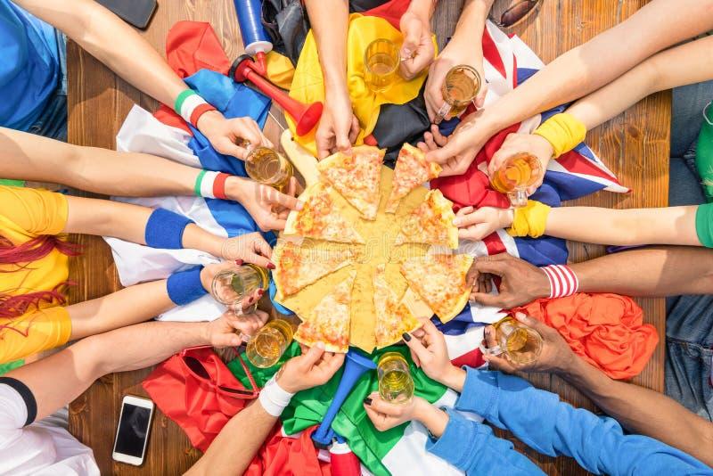 Vue supérieure des mains multi-ethniques du défenseur de sport partageant la pizza images stock
