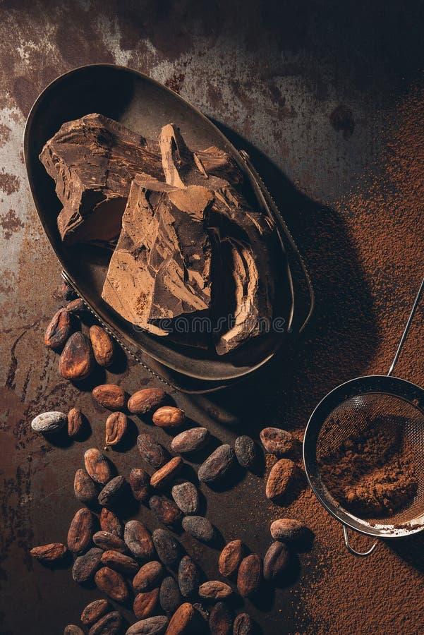 vue supérieure des morceaux de chocolat, des graines de cacao, de la poudre et du tamis délicieux sur le noir photo libre de droits