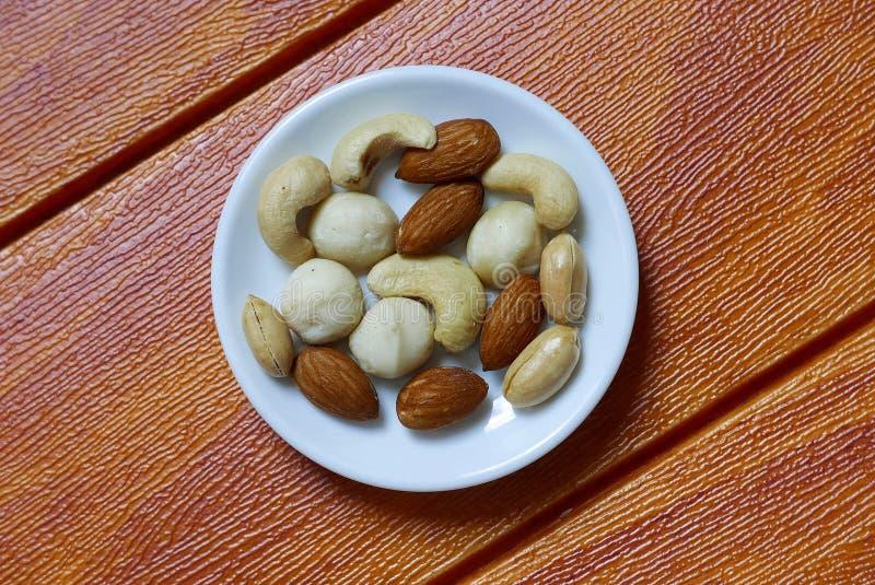 Vue supérieure des noix du Queensland, d'anarcadier, d'amande et d'arachides dans la cuvette sur le fond en bois image stock