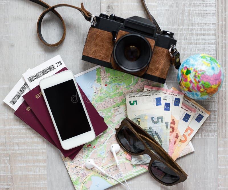 vue supérieure des objets de voyage au-dessus de fond en bois - caméra, carte, argent, passeport, lunettes de soleil et téléphone photographie stock libre de droits