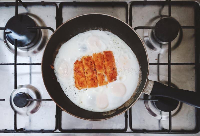 Vue supérieure des oeufs au plat et des bâtons de poisson dans une casserole sur une cuisinière à gaz en acier image stock