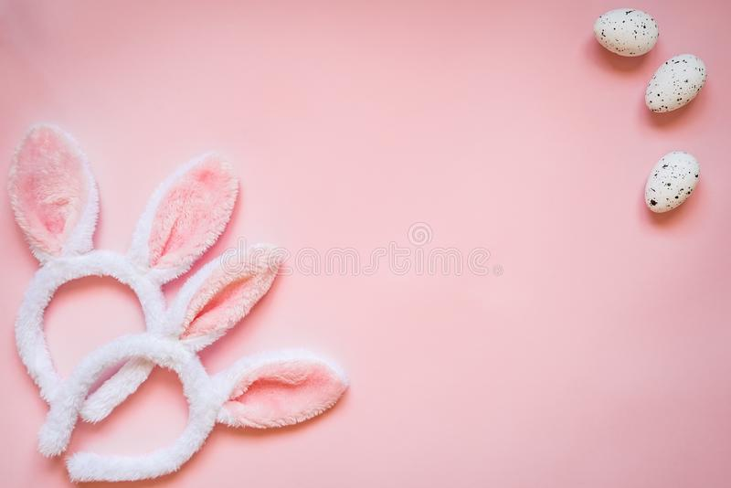 Vue supérieure des oeufs de pâques et de deux oreilles pelucheuses blanches de lapin au-dessus de fond rose Copiez l'espace photographie stock