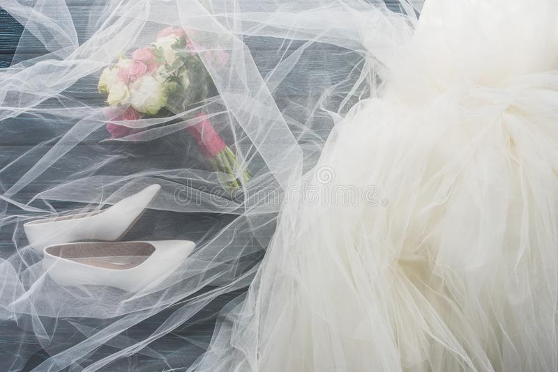 vue supérieure des paires des chaussures, de la robe de mariage et du bouquet sur l'obscurité en bois photo stock