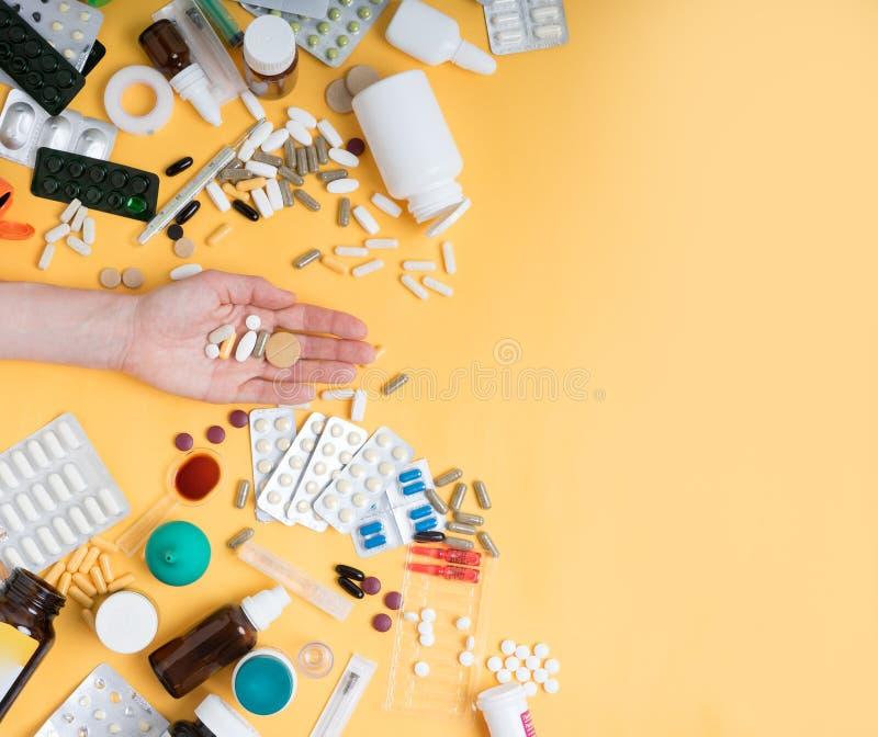 Vue supérieure des pilules femelles de comprimé de participation de main sur le fond jaune comprimés, pilules, médecines et d'aut image stock