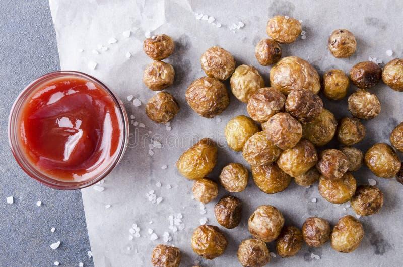 Vue supérieure des pommes de terre de primeurs rôties savoureuses avec du sel sur le papier de cuisson, cuvette avec le ketchup s images stock