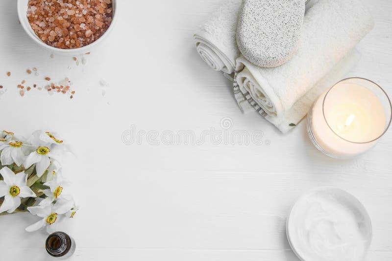 Vue supérieure des produits organiques de soins de la peau avec du sel, bougie, fleurs photos stock