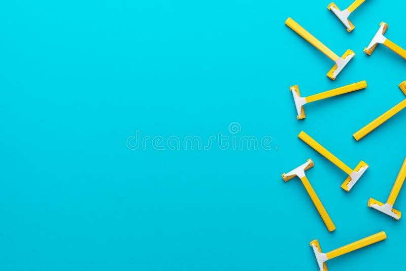 Vue supérieure des rasoirs unisex jetables jaunes sur fond bleu avec espace de copie photos libres de droits