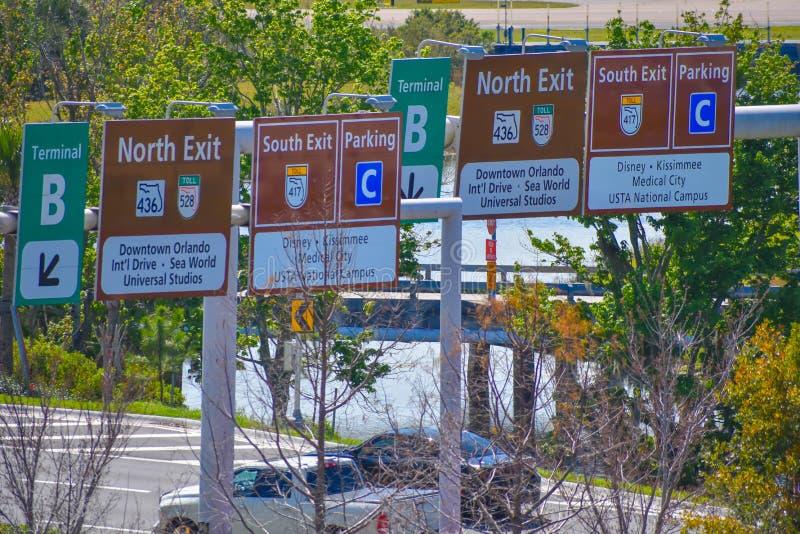 Vue supérieure des signes du terminal B, du stationnement C, du sud et du nord de sortie chez Orlando International Airport image libre de droits