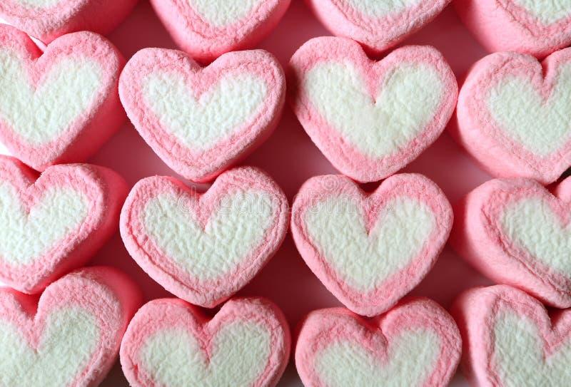Vue supérieure des sucreries en forme de coeur de rose et blanches en pastel alignées de guimauve pour le fond image libre de droits