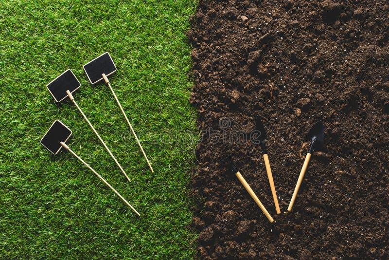 vue supérieure des tableaux noirs vides sur l'herbe et les outils de jardinage sur le sol images libres de droits