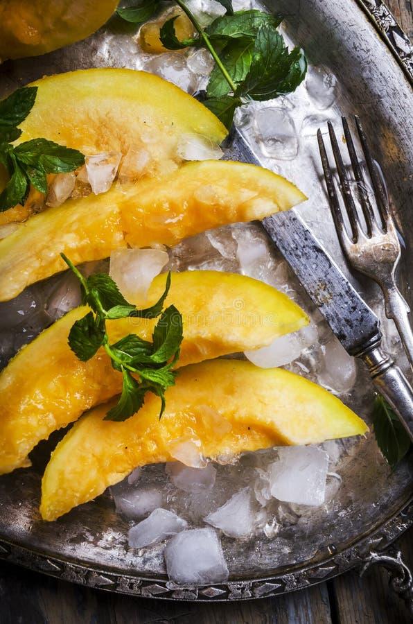 Vue supérieure des tranches de melon de cantaloup avec la menthe et la glace servies du plat de ruban de cru photo libre de droits