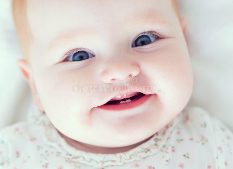 Vue supérieure du bébé infantile, smilyng avec ses deux premières dents image stock