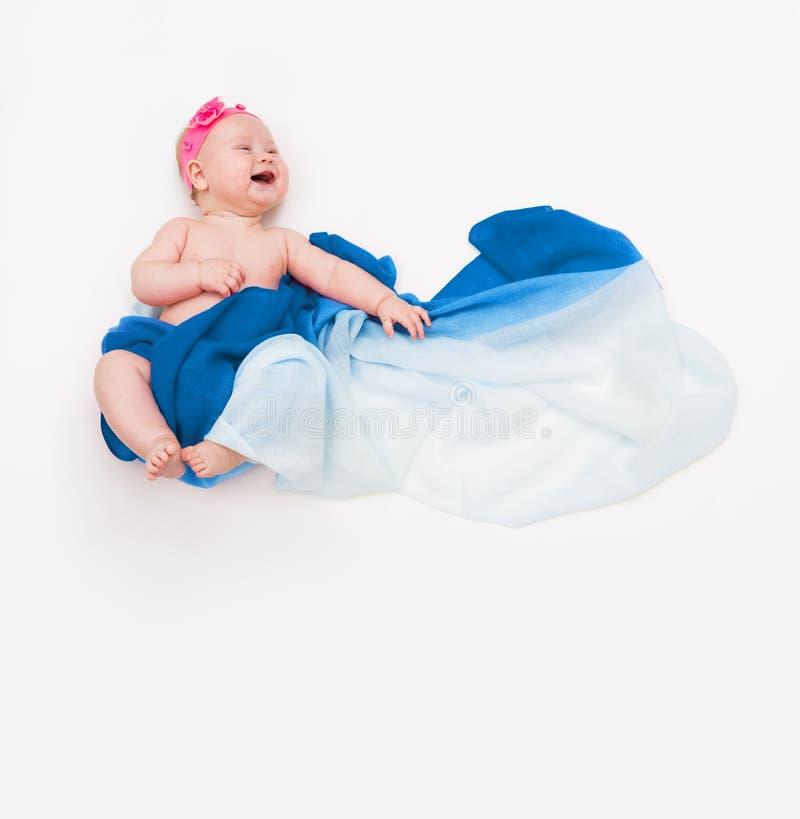 Vue supérieure du bébé riant infantile mignon enveloppé dans une écharpe bleue dépeignant un nuage photographie stock libre de droits