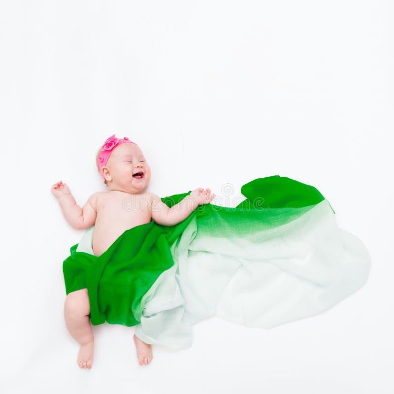 Vue supérieure du bébé riant infantile mignon enveloppé dans une écharpe verte dépeignant un nuage photo stock