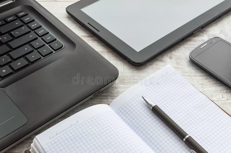 Vue supérieure du bureau blanc avec l'ordinateur portable, le smartphone et le comprimé images stock