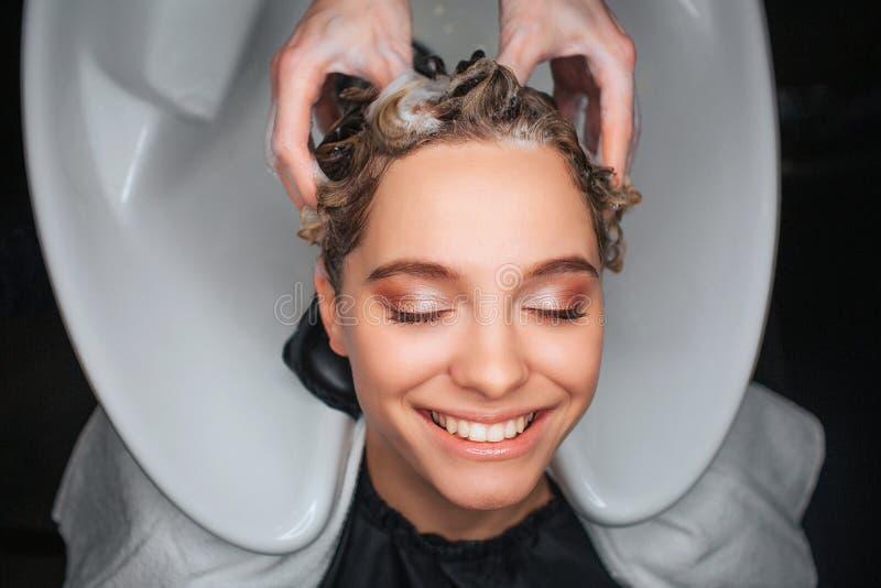 Vue supérieure du client féminin heureux souriant avec les yeux fermés tandis que coiffeur massant des cheveux Jeune femme détend images libres de droits