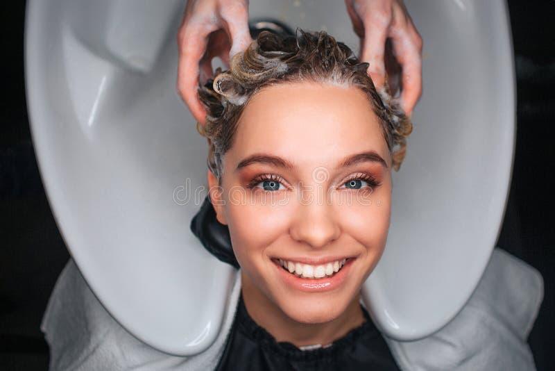 Vue supérieure du coiffeur de sourire de moment de client féminin heureux massant des cheveux Jeune femme se reposant dans le sal photos libres de droits