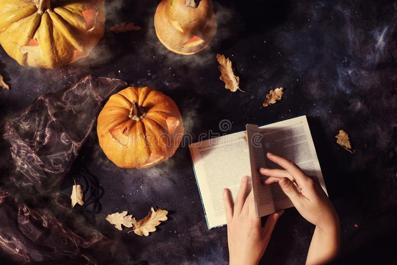Vue supérieure du livre de lecture de femme entouré par des potirons de Halloween image stock