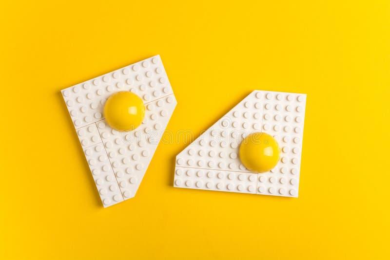 Vue supérieure du plat blanc avec des oeufs au plat de concepteur du ` s d'enfants sur le fond de papier jaune photographie stock libre de droits