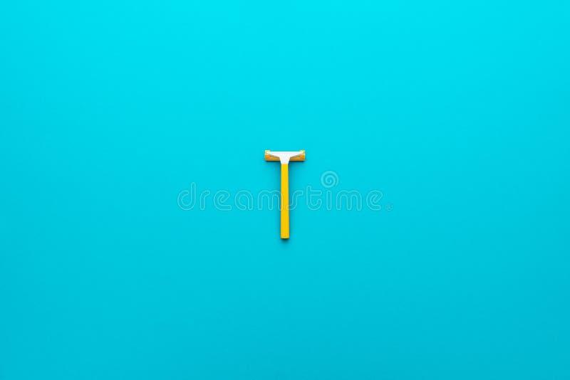 Vue supérieure du rasoir unisex jetable jaune sur fond bleu avec espace de copie photo stock