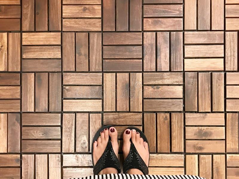 Vue supérieure du selfie des pieds avec la chaussure de pantoufle sur le plancher en bois images stock