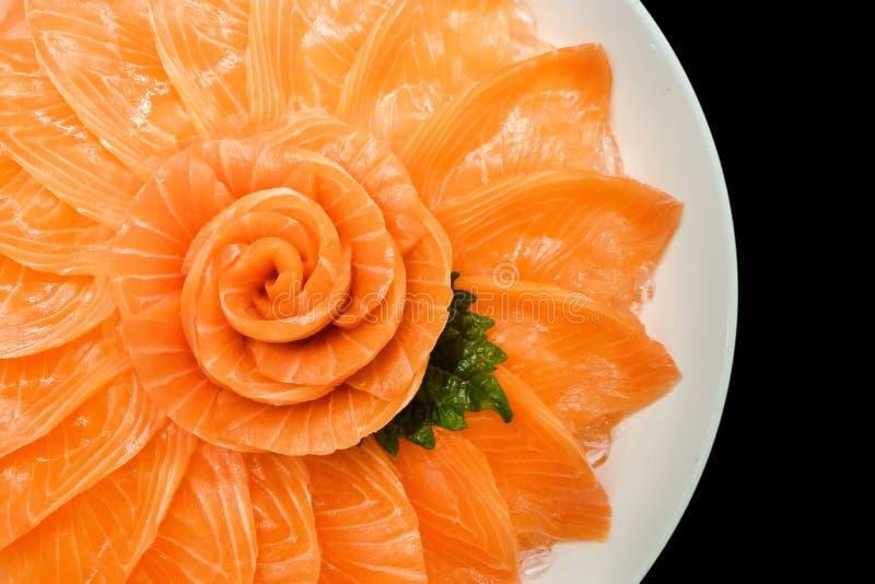 Vue supérieure du service saumoné de sashimi sur la forme de fleur dans le bateau blanc de cuvette de glace d'isolement sur le fo photos stock