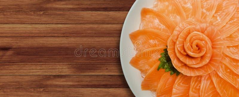Vue supérieure du service saumoné de sashimi sur la forme de fleur dans le bateau blanc de cuvette de glace sur le fond en bois d photo libre de droits
