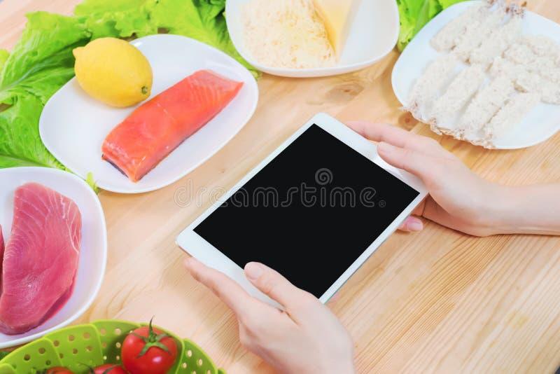 Vue supérieure en gros plan des mains femelles tenant une tablette avec une affichage neutre entourée par la nourriture saine sur image stock