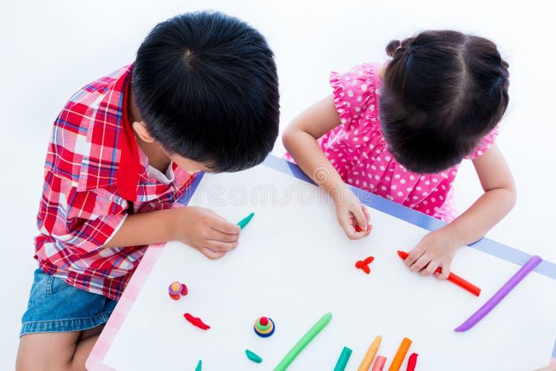 Vue supérieure Enfants asiatiques jouant avec de l'argile de jeu sur la table renforcez photographie stock libre de droits