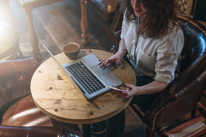 Vue supérieure, jeune femme d'affaires dans la chemise blanche se reposant au bureau et travaillant en ligne sur l'ordinateur por image libre de droits