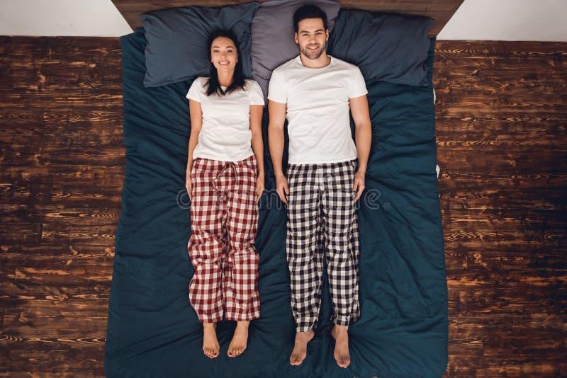 Vue supérieure L'homme bel et la belle femme dans le pantalon de pyjama se trouvent tout droit lit et recherchent photographie stock