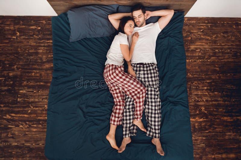 Vue supérieure La belle jeune femme se trouve à côté de l'homme bel Poses de sommeil pour des couples photographie stock
