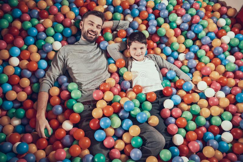 Vue supérieure Papa et fils heureux dans la piscine avec des boules photographie stock