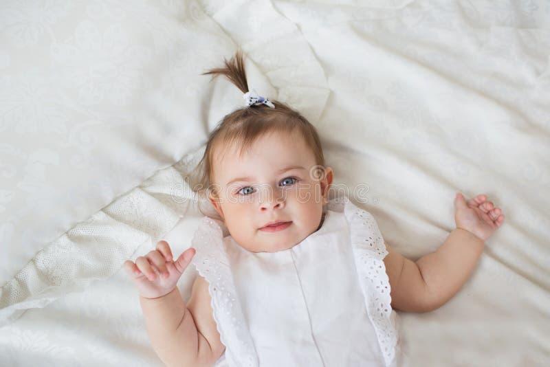 VUE SUPÉRIEURE : Portrait de petite fille dans une robe blanche sur un lit image stock