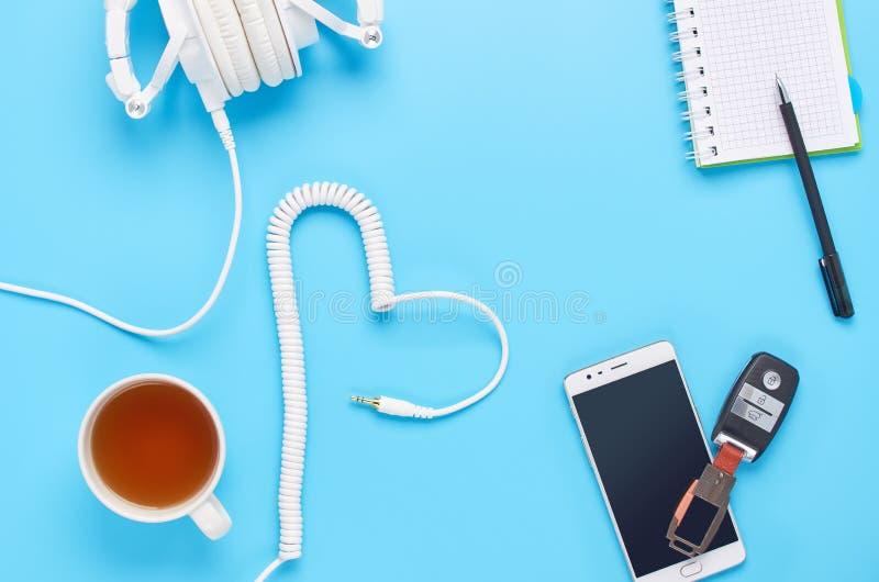 Vue supérieure sur des instruments sur le fond bleu, la composition des écouteurs blancs, le téléphone, le comprimé, le verre ave photographie stock