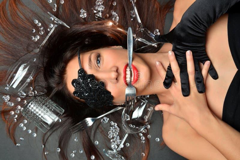 Vue supérieure sur une jeune belle brune se situant dans les gemmes de placer, fourchettes de couverts, verres pour le vin photos libres de droits