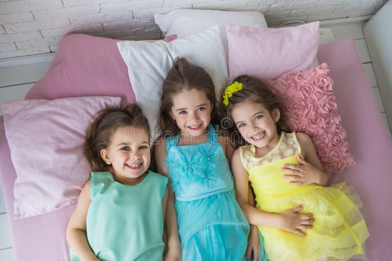 VUE SUPÉRIEURE : Trois filles assez petites dans les robes colorées se trouvent sur un lit et sourient images stock