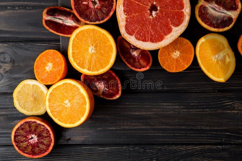 Vue sup?rieure, configuration plate, macro Oranges juteuses coupées en tranches, mandarines, pamplemousse Fond fonc? Copiez l'esp photographie stock libre de droits