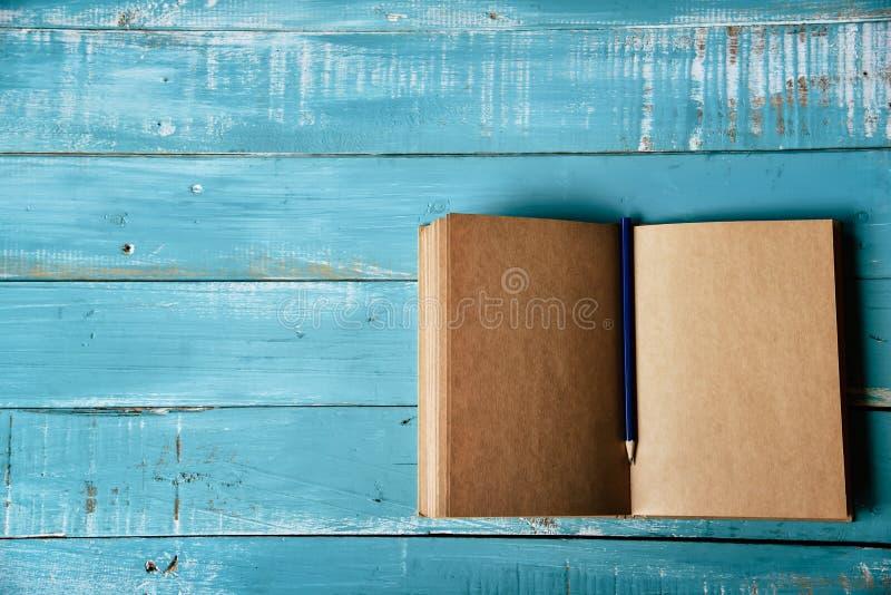 Vue sup?rieure de carnet ouvert vide sur le fond en bois bleu avec le crayon pourpre au milieu Bureau fonctionnant de papeterie ? image libre de droits