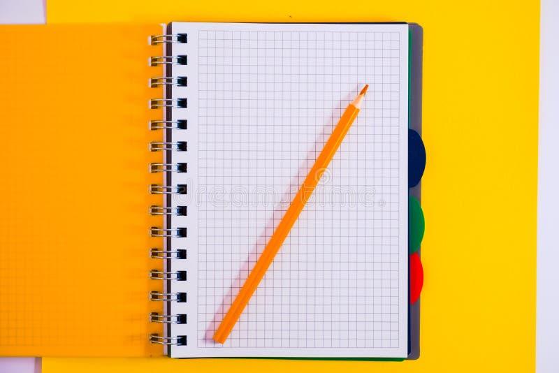 Vue sup?rieure de carnet vide en spirale ouvert avec le crayon sur le fond jaune de bureau photos stock