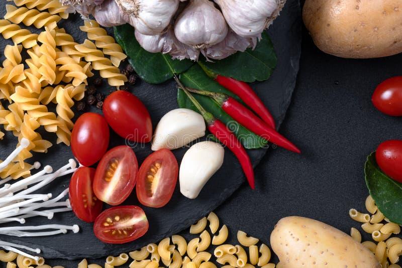 Vue sup?rieure des ingr?dients frais Fond à cuire sain avec les légumes et les pâtes organiques pour le vegan sur l'ardoise noire photos stock