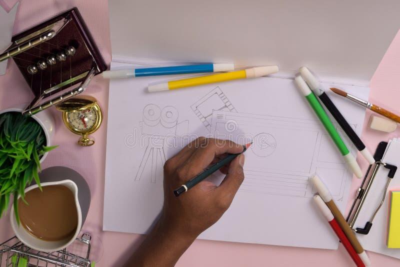 Vue sup?rieure des mains de l'homme dessinant sur une table rose, pr?parant pour faire le travail dans un carnet ouvert image stock