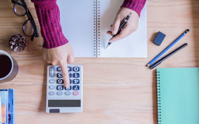 Vue sup?rieure Femme de main utilisant des finances et calculatrice sur le bureau de table ? la maison photos stock