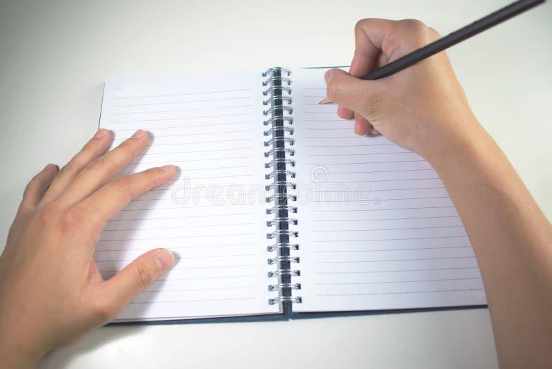 Vue sup?rieure La main écrit un livre avec le crayon noir photos stock