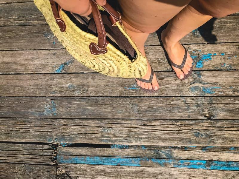 Vue sup?rieure, photo des jambes dans des bascules de plage et avec un sac de paille ? disposition sur un vieux plancher en bois  image libre de droits