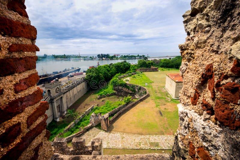 Vue sur de vieux murs de ville et nouveau port industriel de Santo Domingo, par la fenêtre de la forteresse - Fortaleza photo libre de droits
