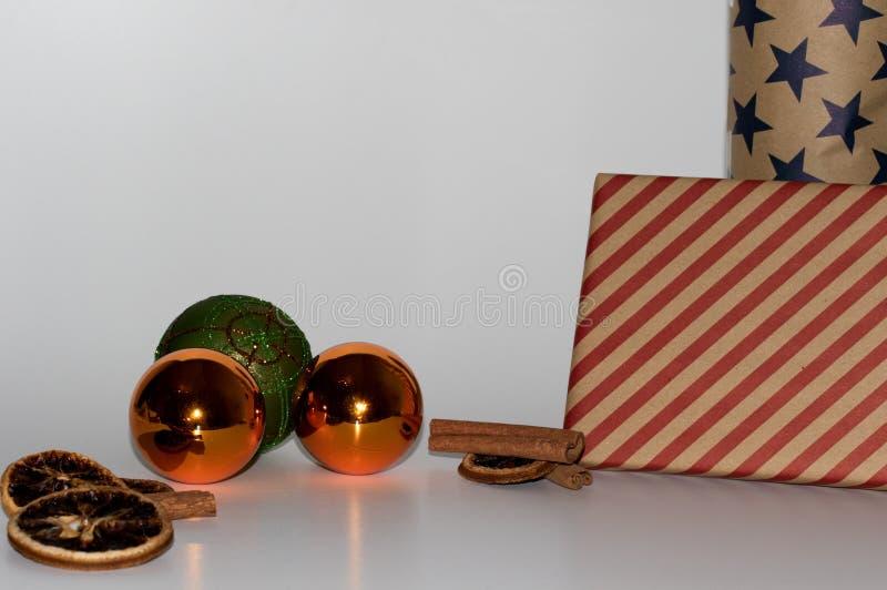 Vue sur des certaines boules de Noël et décoration oranges et vertes de Noël et avec deux présents et avec un fond blanc et desso image stock