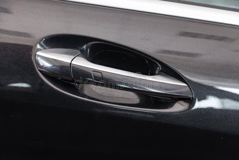 Vue sur l'entrée principale noire fermée avec la poignée avec l'accès keyless fait à partir du chrome de la voiture de luxe après photos libres de droits