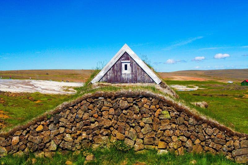 Vue sur la maison en bois de gazon construite sur la pile des pierres naturelles contre le ciel bleu images libres de droits